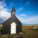 Church security; Church building in field, Black church with a white door